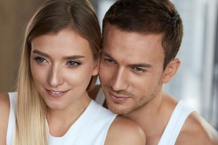 愛し、ケアします。クローズ アップ幸せな美しい素敵なカップル。新鮮な柔らかい顔の皮膚とハンサムな男と女は一緒に笑って。ロマンチックな関