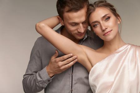身体衛生。ハンサムな男の脇にきれいな柔らかい肌を持つ美しい笑みを浮かべて女性を Caressing します。男性のセクシーな女の子の脇の下に優しく触 写真素材