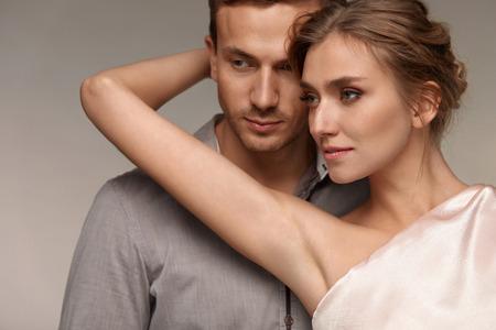 美しい夫婦愛。完璧な自然なメイクとセクシーな若い女性の近くにハンサムな男は。女性の腕を保持と脇の滑らかな柔らかい純粋な肌を見せてのク
