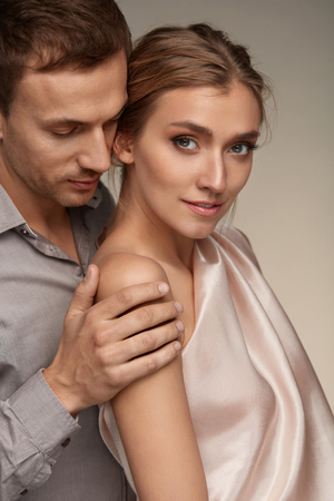sensually: Romantic Couple In Love. Handsome Man Gently And Sensually Holding Beautiful Woman With Perfect Natural Makeup. Male Touching Female Smooth Soft Healthy Skin On Arm. Beauty Cosmetics. High Resolution
