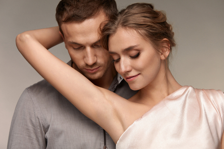 Beautiful Couple In Love. Handsome Man Close To Sexy Young Woman With Perfect Natural Makeup. Closeup Of Female Holding Arm And Showing Smooth Soft Pure Skin On Armpits. Skin Care. High Resolution