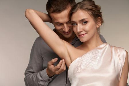 Körperhygiene. Stattlicher Mann Streicheln schöne lächelnde Frau mit Sauber Soft Skin On Achsel. Male sanft berühren Sexy Girl Achsel. Frau mit einer Frische Glatte seidige Haut. Verliebtes Pärchen. Hohe Auflösung
