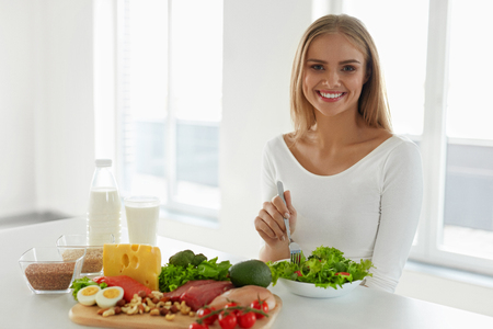 food healthy: Nutrition. Beautiful Woman On Healthy Diet With Organic Green Vegetable Salad In Kitchen. Smiling Girl Sitting At Table With Different Food Ingredients, Variety Of Foods And Products. High Resolution