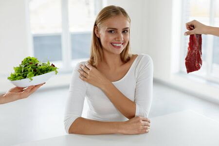 meat diet: Healthy Diet. Beautiful Smiling Woman Sitting At Table, Female Hands Holding Raw Meat And Green Vegetable Salad. Attractive Girl With Food Products In Kitchen. Nutrition Concept. High Resolution