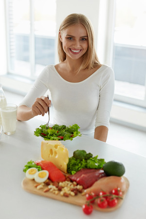 niña comiendo: Healthy Nutrition. Beautiful Woman On Diet Eating Organic Green Vegetable Salad In Kitchen. Happy Smiling Girl Sitting At Table With Different Food Products And Ingredients. High Resolution