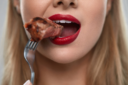 Eating Meat. Closeup Of Woman Mouth With Red Lips, White Teeth Biting Tasty Beef Steak On Fork. Close-up Of Beautiful Female Mouth Eating Delicious Grilled Meat. Nutrition Concept. High Resolution