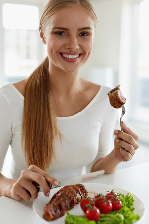 eating dinner: Woman Eating Food. Beautiful Smiling Female Having For Dinner Delicious Grilled Meat With Fresh Vegetables In Kitchen. Healthy Attractive Girl Dining Having Beef Steak With Tomatoes, Salad. Nutrition