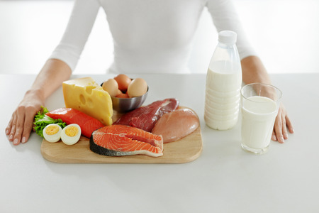 Healthy Foods. Closeup Of Female Hands At Table With Different Food Products And Ingredients. Close-up Of Woman Hands With Fresh Raw Meat, Fish And Dairy Products In Kitchen. High Resolution