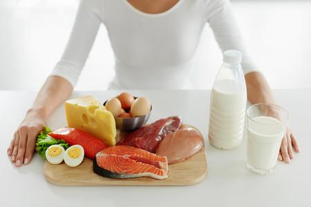 健康食品。さまざまな食品や食材とのテーブルで女性の手のクローズ アップ。新鮮な生の肉、魚、乳製品の台所で女性の手のクローズ アップ。高分 写真素材