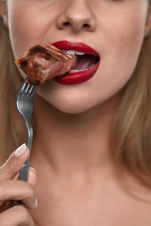 女性の食べる肉。美しい顔、赤い唇を健康的な空腹の少女のクローズ アップは、おいしい焼き肉を食べる。フォークのおいしいステーキの部分をか