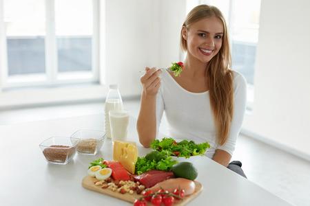carnes y verduras: Nutrición. Mujer Hermosa En Orgánica dieta saludable con ensalada de verduras verdes en la cocina. La tabla que se sienta en la sonrisa con diferentes ingredientes de alimentos, variedad de alimentos y productos. Alta resolución Foto de archivo
