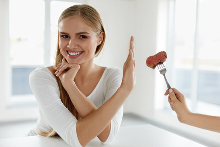 Beautiful Woman Refuses To Eat Red Meat. Female Hand Holding Fork With Piece Of Beef Steak, Proposing It To Girl. Attractive Female With Stop Hand Sign. Vegetarian Nutrition Concept. High Resolution