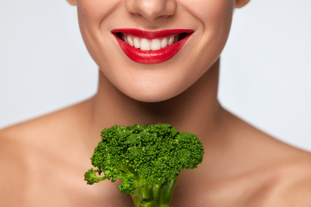 Healthy Diet. Beautiful Smiling Woman Face With Fresh Organic Broccoli. Closeup Of Female Mouth With Red Lips, White Teeth With Green Vegetable. Healthy Nutrition And Health Concept. High Resolution Stock Photo