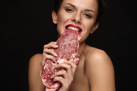 먹는 고기. 원시 고기를 먹고 갈 빨간 입술 배고픈 여자. 그녀의 이빨을 가진 쇠고기 스테이크 고기를 무시 아름 다운 얼굴 메이크업으로 여자의 초상