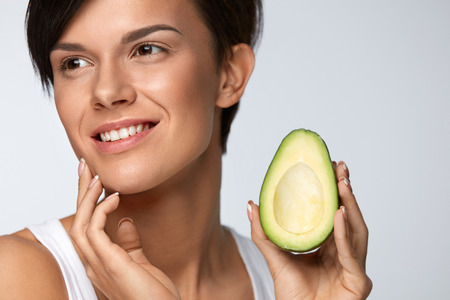 beauty skin: Skin Care And Beauty. Beautiful Happy Woman With Smooth Soft Clean Skin, Natural Makeup Holding Organic Green Avocado In Hand At Face. Healthy Lifestyle And Nutrition, Health Concept. High Resolution