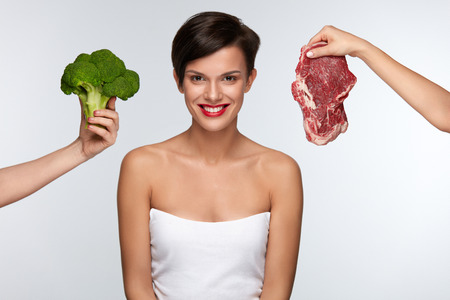 whether: Healthy Eating. Beautiful Woman With Red Lips Choosing Between Raw Meat And Broccoli, Thinking Whether To Eat Vegetables Or Meat. Female Hands Holding Food Products. Nutrition Concept. High Resolution Stock Photo
