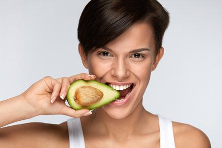 ダイエット栄養。美しい笑顔の女性は、有機緑のアボカドをかみます。柔らかい肌、新鮮な自然の顔メイク アボカドを食べると幸せなベジタリアン
