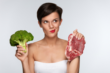 健康的な食事。赤い唇生の肉とブロッコリーの間を選択する、野菜や肉を食べるのかを考えると美しい女性。女の子の手で食品を保持します。ダイ