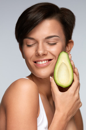 cosmetic product: Healthy Foods. Beautiful Smiling Woman With Fresh Soft Skin Holding Organic Green Avocado. Portrait Of Attractive Happy Girl With Vegetable In Hand. Diet Nutrition, Health Concept. High Resolution