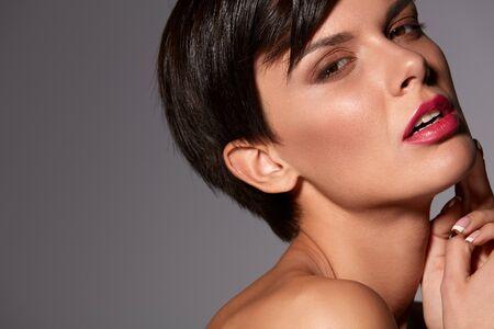 labios sexy: La belleza de la cara de la mujer. Retrato de muchacha hermosa modelo con maquillaje brillante facial glamour, suave de la piel sana, labios de color rosa atractiva que presenta sobre fondo gris. Cosméticos y el concepto de cuidado de la piel. Alta resolución