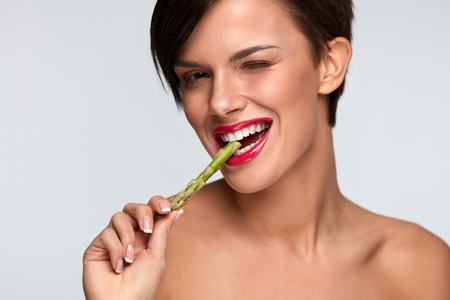 nutrition health: Woman On Diet Nutrition. Healthy Eating Girl With Beautiful Face, Pink Lips, White Teeth Biting Green Fresh Asparagus. Smiling Female Eating Vegetable. Good Food For Health And Beauty. High Resolution