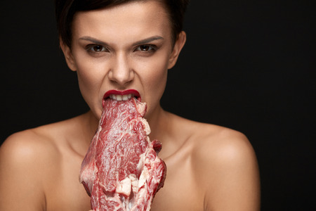 Eating Meat. Hungry Woman With Red Lips Going To Eat Raw Meat. Portrait Of Girl With Beautiful Face Makeup Biting Beef Steak Meat With Her Teeth. High Protein Diet And Food Concept. High Resolution