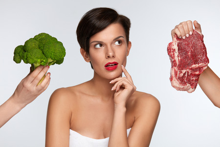 Healthy Eating. Beautiful Woman With Red Lips Choosing Between Raw Meat And Broccoli, Thinking Whether To Eat Vegetables Or Meat. Female Hands Holding Food Products. Nutrition Concept. High Resolution Stock Photo