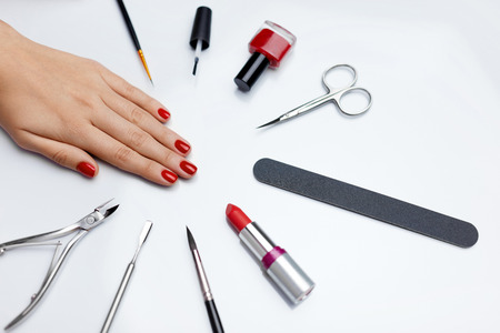 Professional Manicure. Closeup Of Beautiful Womans Nails With Red Nail Polish With Nail Care Tools On White Table. Close-up Of Female Hand With Perfect Healthy Nails. Beauty Care. High Resolution Reklamní fotografie
