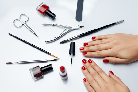 Woman Hands Care. Top View Of Beautiful Smooth Womans Hands With Professional Nail Care Tools For Manicure On White Background. Closeup Of Healthy Female Nails With Red Nail Polish. High Resolution Reklamní fotografie
