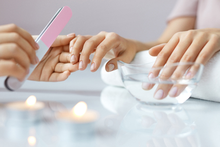 Woman Hand Care. Closeup Of Beautiful Female Hands Having Spa Manicure At Beauty Salon. Beautician Filing Clients Healthy Natural Nails With Nail File. Nail Treatment. High Resolution Stock Photo