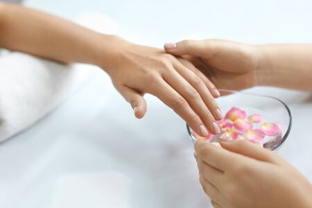 Nail Care. Woman Receiving Manicure Procedure In Spa Salon. Closeup Of Female Hands Getting Hand Massage From Beautician Near Aroma Bath For Hands With Flower Petals. High Resolution