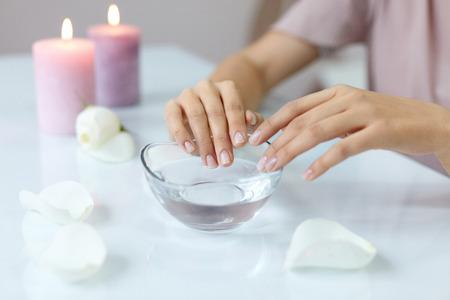 Nagelverzorging. Close-up van mooie vrouw handen met natuurlijke nagels in schoonheidssalon. Vrouwelijke doorwekende vingernagels in transparante glazen kom vol water binnenshuis. Spa Manicure Concept. Hoge resolutie