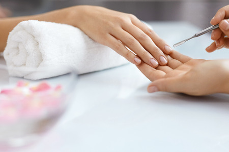Nail Care At Beauty Salon. Woman Receiving Professional Manicure From Nail Specialist. Closeup Of Female Getting Cuticle Removing Procedure With Metal Pusher Tool. Healthy Fingernails. High Resolution