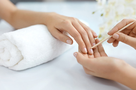 Nail Salon. Closeup Of Beautician Hands Cleaning Female Clients Nails With Orange Wooden Stick, Cuticle Pusher, Removing Cuticles In Beauty Salon. Woman Hands Nail Care And Manicure. High Resolution