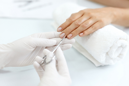 ネイルケアします。女性のクライアントの爪から切削キューティクルの金属化粧品爪のはさみを使用して美容師の手のクローズ アップ。マニキュア