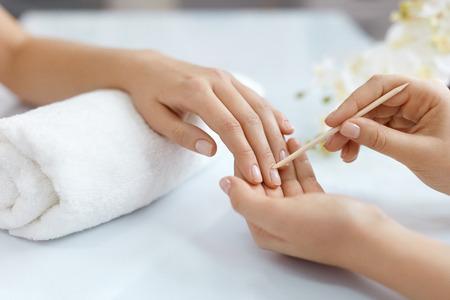 큐티클 리무버. 여자의 손에 매니큐어를 받고 손 치료 절차를 손톱. 근접 매니큐어 뷰티 살롱에서 큐티 클 나무 스틱으로 여성 손톱에 큐티를 밀어. 높