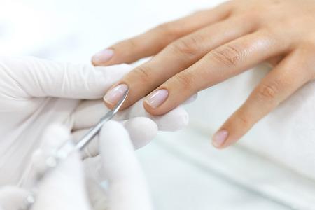 マニキュア。プロの金属爪のはさみと女性の爪からキューティクルを削除するネイリストの手のクローズ アップ。健康的な自然な女性の手の爪取得