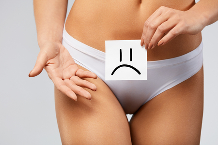 gynecological: Woman Health Problem. ?loseup Of Female With Fit Slim Body In Panties Holding White Card With Sad Smiley Face Near Her Stomach. Digestive Disorders, Period Pain, Health Issues Concept. High Resolution