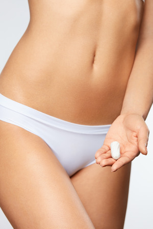 Female Health Care Product. Closeup Of Beautiful Fit Slim Woman Body In White Panties Holding Tampon. Girl In Underwear With Period Product In Hand. Feminine Intimate Hygiene Concept. High Resolution