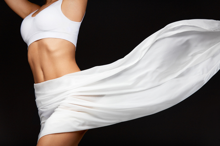 Woman Body Care. Beautiful Healthy Female With Perfect Fit Slim Body Shape, Silky Smooth Soft Skin In White Bikini Underwear And Flying Textile On Black Background. Health Concept. High Resolution