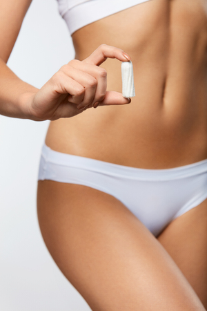 Female Period Protection. ?loseup Of Slim Woman Body In White Panties Holding Clean Tampon In Hand. Beautiful Female Body In Underwear Holding Feminine Hygiene Product. Women Health. High Resolution Stock Photo
