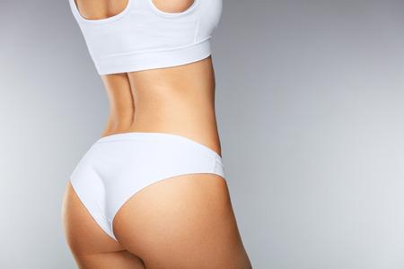 体のケア。スリム美人はタイトなしっかりしたお尻、セクシーなお尻、白いビキニパンツで健康的な柔らかい肌に戻る。下着姿で完璧なボディ形状 写真素材