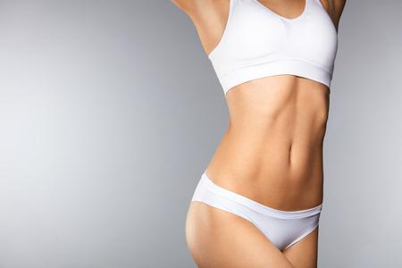 Lichaamsverzorging. Mooie Vrouw In Vorm Met Fit Slim Body, Gezonde Gladde Zachte Huid In Witte Bikini Panties Op Grijze Achtergrond. Close-up Vrouwelijk Lichaam In Ondergoed. Gezondheids- en dieetconcepten. Hoge resolutie Stockfoto