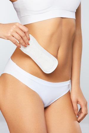 manos limpias: Higiene Femenina. ? De la mujer hermosa con el cuerpo delgado apto en la ropa interior blanca que sostiene la toalla sanitaria, Panty Liner en manos. Muchacha que lleva a cabo el cojín limpio del período, producto íntimo femenino. Alta resolución
