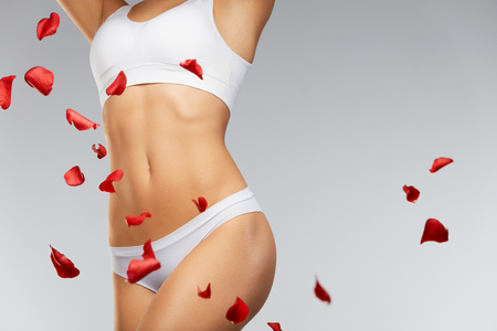 mujer con rosas: Woman Body Care. Beautiful Female Body In Shape With Fit Slim Figure, Smooth Soft Skin In Bikini Panties With Flying White And Red Rose Flower Petals. Closeup Girls Body In Underwear. High Resolution Foto de archivo