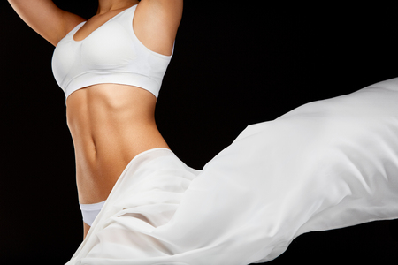 Woman Body Care. Beautiful Healthy Female With Perfect Fit Slim Body Shape, Silky Smooth Soft Skin In White Bikini Underwear And Flying Textile On Black Background. Health Concept. High Resolution Reklamní fotografie - 74374517