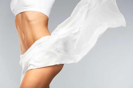 Frauen Gesundheit. Schöne gesunde Frau mit Fit schlanke Körper, seidig glatte weiche Haut in weißen Bikini Unterwäsche. Nahaufnahme Des Textils Fliegen Auf Perfekte Weibliche Körperform. Körperpflege-Konzept. Hohe Auflösung Standard-Bild