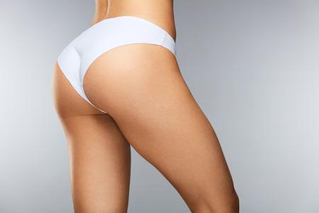 바디 케어. 타이트 기업 엉덩이, 섹시한 엉덩이, 화이트 비키니 팬티에 건강한 부드러운 피부와 아름 다운 슬림 여자로 돌아 가기. 속옷에서 완벽한 바