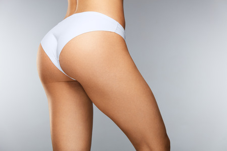 Lichaamsverzorging. Mooie slanke vrouw terug met strakke stevige billen, Sexy Butt, gezonde Soft Skin in witte bikini slipje. Close-up Meisje Met Perfect Body Shape In Ondergoed. Beauty Concept. Hoge resolutie Stockfoto