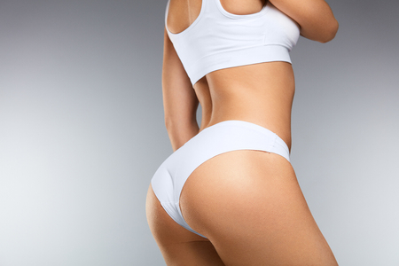 Schöner Frauenkörper In Form. Gesundes Mädchen mit schlankem Körper, weicher Haut und festem Gesäß, Hüften im weißen Bikinihöschen. Frau mit sexy Rücken, engen großen Hintern in Unterwäsche. Hohe Auflösung